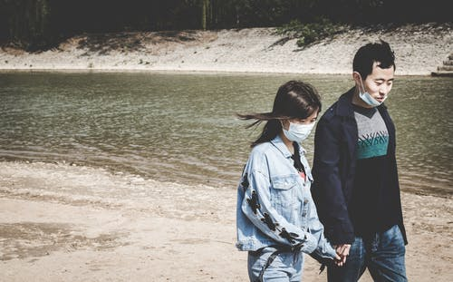 Asian couple in masks holding hands while walking near river
