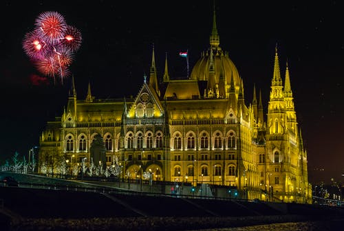 Old stone house facade under sky with bright fireworks during festive event in Budapest at dusk