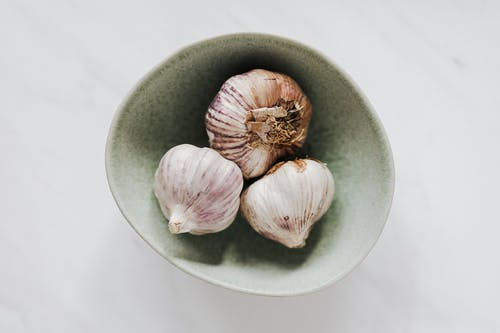 Bowl of garlic bulbs on marble table