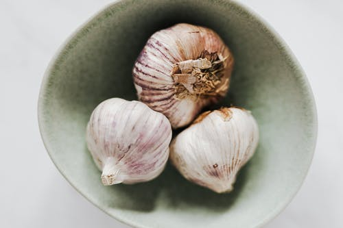 Bowl with whole garlic heads on table