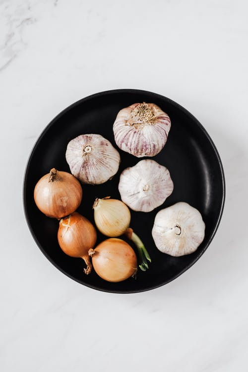 Overhead of raw unpeeled aromatic garlic and yellow onions with one regrowing onion bulb on black ceramic plate placed on white marble background