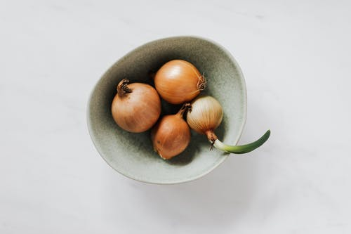 Bowl with raw onion bulbs on marble surface