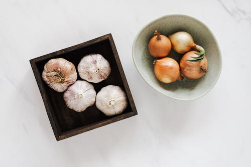 Assorted organic onions and garlic on marble background