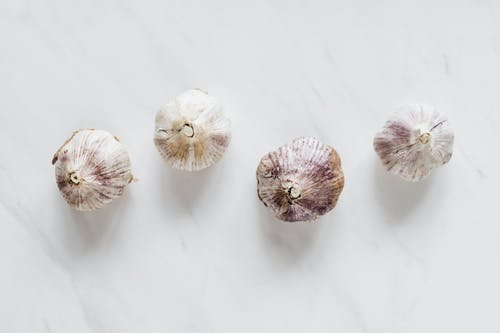 Top view of raw whole unpeeled aromatic garlic placed next to each other on white marble surface before cooking process