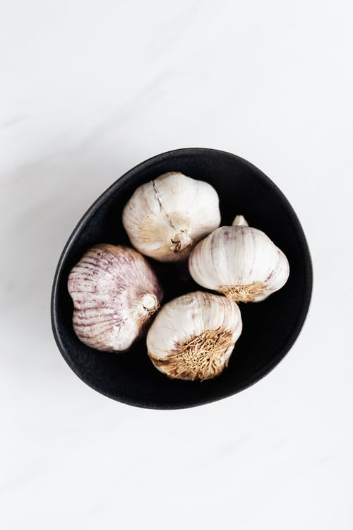 Top view of raw whole fragrant flavorful unpeeled fresh garlic in black bowl placed on white marble table under bright light