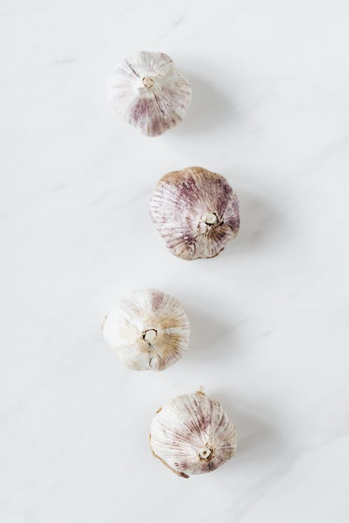 Top view of fresh raw aromatic unpeeled whole garlic bulbs arranged in zigzag line while placed on white marble background