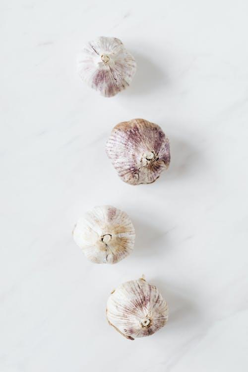 Raw garlic on white marble table