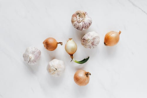Top view composition of raw unpeeled ripe yellow onions and fresh whole aromatic garlic bulbs placed on white marble background