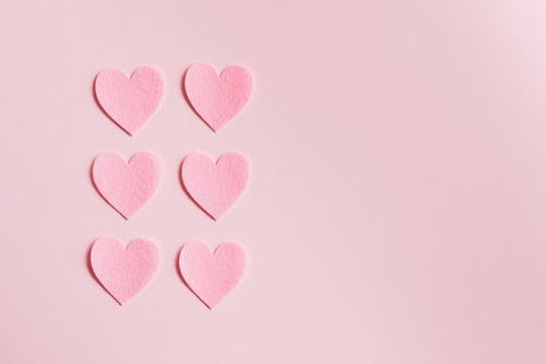 Pink paper hearts on light pink surface