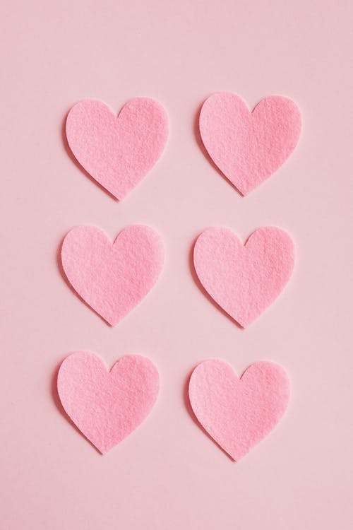 Bright pink heart shaped cutouts on pink background