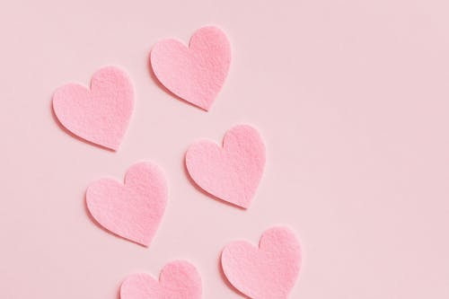 Heartshaped paper cutouts on pink background