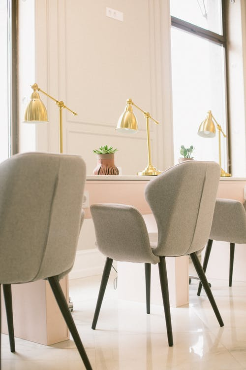 Comfortable pastel colored armchairs placed near stylish light pink desk with golden lamps and plant pots against big windows on sunny morning