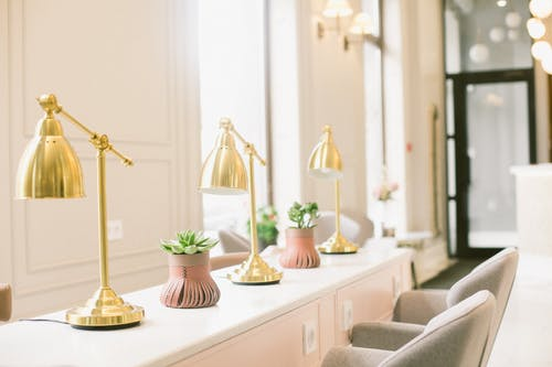 Classic interior design of stylish beauty salon with light pink desk with white desktop golden lamps and stylish plants near cozy comfortable chairs in beauty salon on sunny day