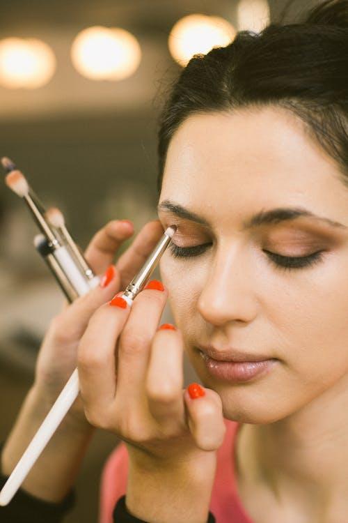 Crop visagiste applying eyeshadow on model eyelid