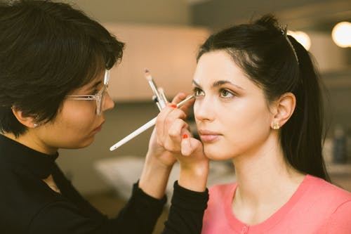 Visagiste applying eyeshadow on model face