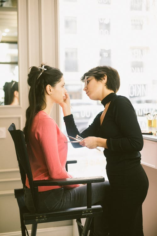Focused visagiste applying eyeshadows on client