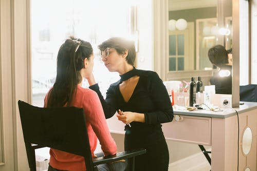 Concentrated female stylist professionally applying makeup on brunette with long hair while working in stylish salon and standing against cozy vanity table with lights