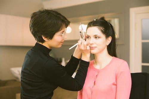 Visagiste applying eyes makeup on model