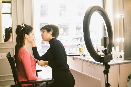 Side view of young concentrated female makeup artist in black casual outfit applying eyeshadow on brunette customer in pink clothes while standing against classic vanity table