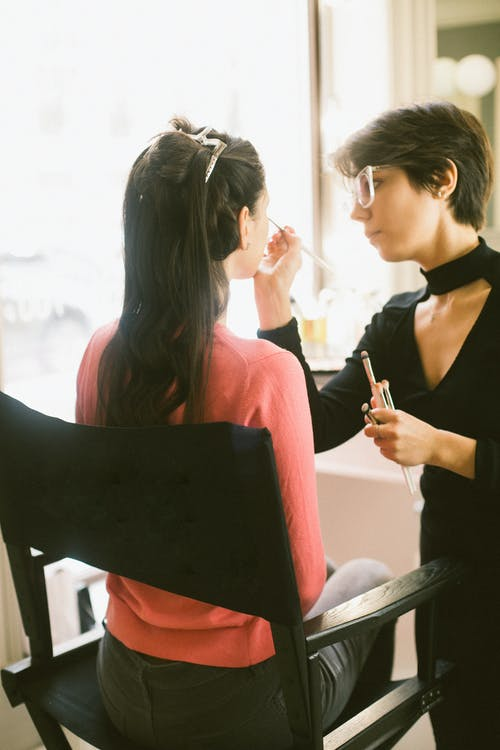Female visagiste applying makeup on model