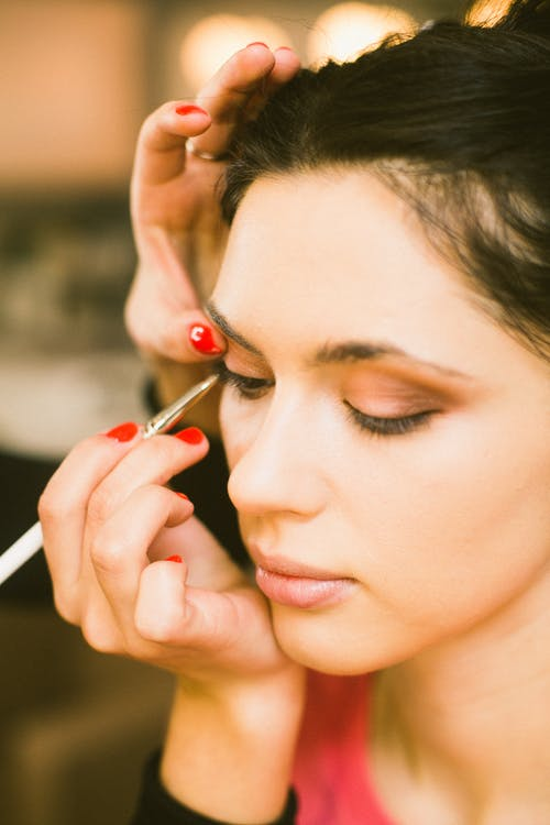 Crop makeup artist applying trendy makeup on model