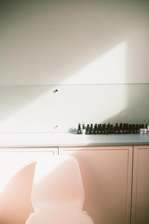 時尚櫃子,靠近粉紅色椅子的指甲油瓶