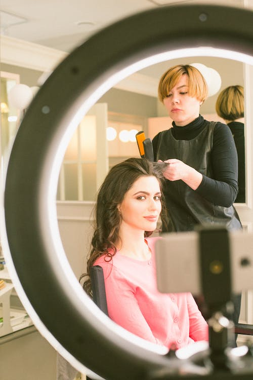 Professional female hairdresser making hairstyle for young lady against light mirror