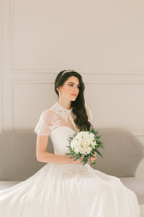 Pensive young bride in wedding dress with bouquet of flowers