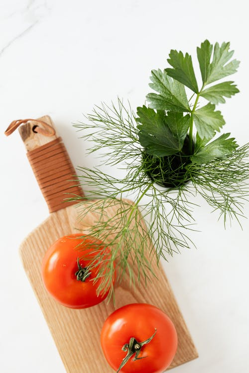 Top view of fresh ripe tomatoes placed on wooden cutting board near bunch of parsley and dill on marble surface