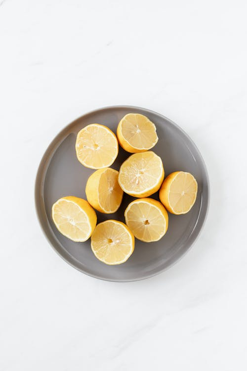 Halved citruses on grey ceramic plate