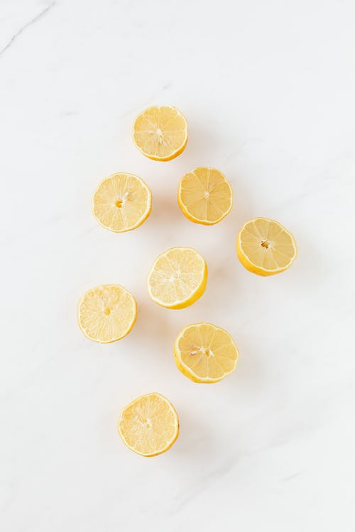 Top view of composition of fresh chaotic lemons placed on white marble texture surface