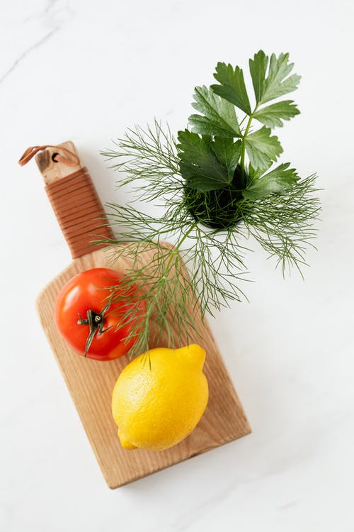 Overhead view of raw tomato and lemon lying on cutting board with dill and parsley in cup beside on marble table