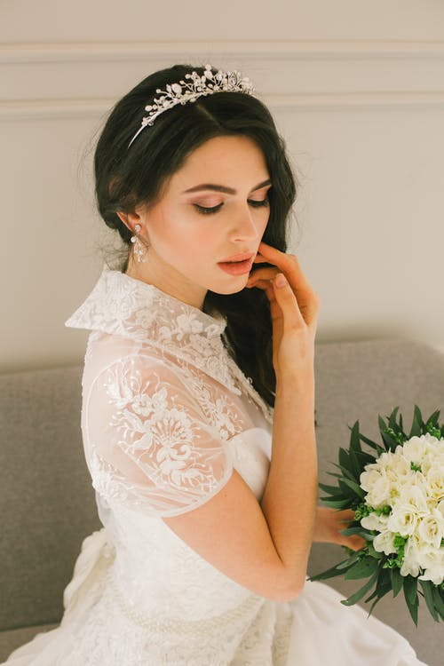 Young bride in diadem with delicate bouquet