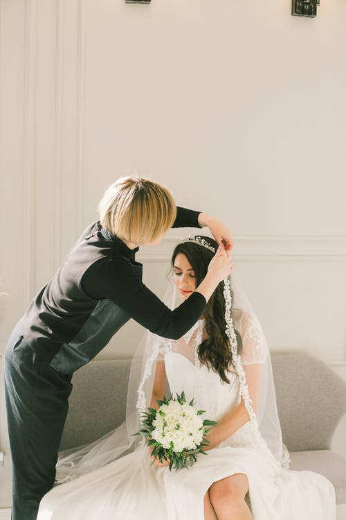 Bride sitting on couch and dressmaker fixing bridal veil
