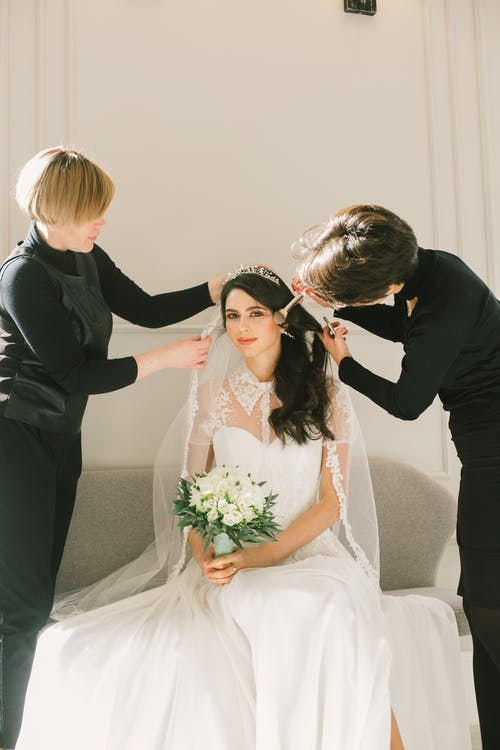 Happy bride in white dress with dressmaker and makeup artist