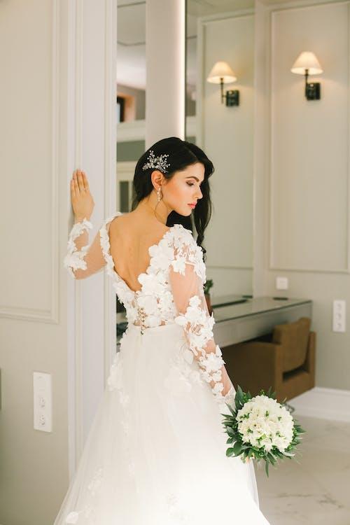 Elegant bride in wedding dress standing in studio