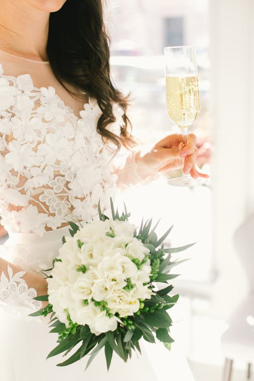 Crop bride with wedding bouquet and champagne