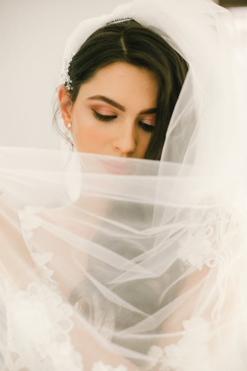 Beautiful young bride covering face with veil while posing