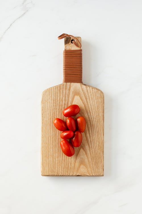 Ripe Datterino tomatoes lying on cutting board on table