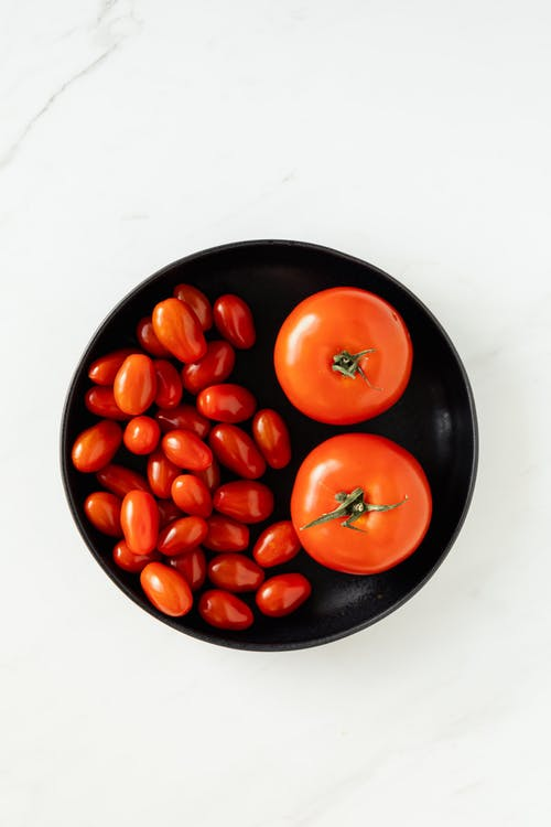 Different sorts of tomatoes in big bowl on table