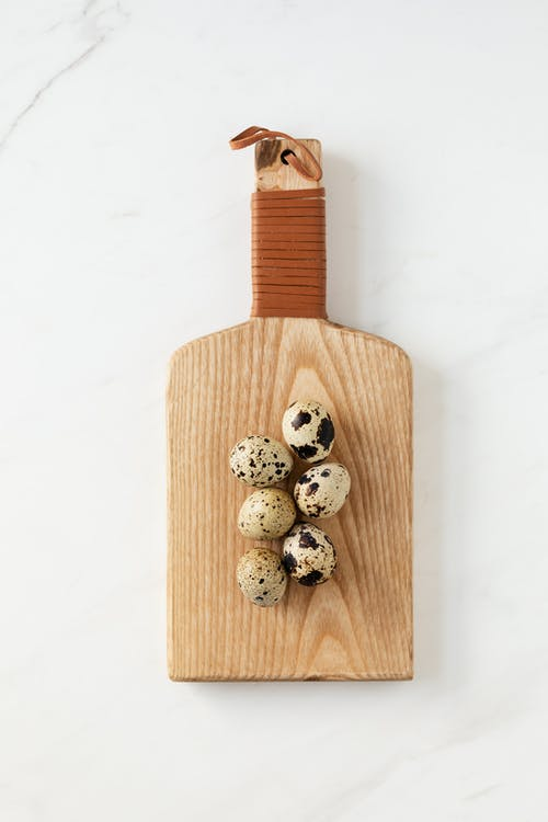 Top view of cutting board with quail eggs lying on white marble table