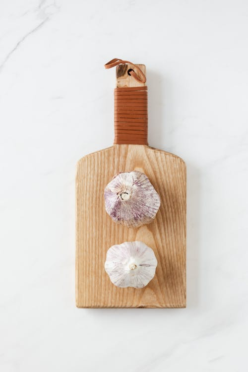 Top view of garlic heads placed on wooden kitchen board on white marble table