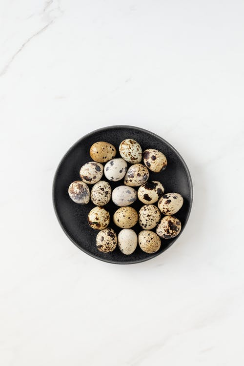 Top view of quail eggs placed in black round bowl standing on white clean marble surface