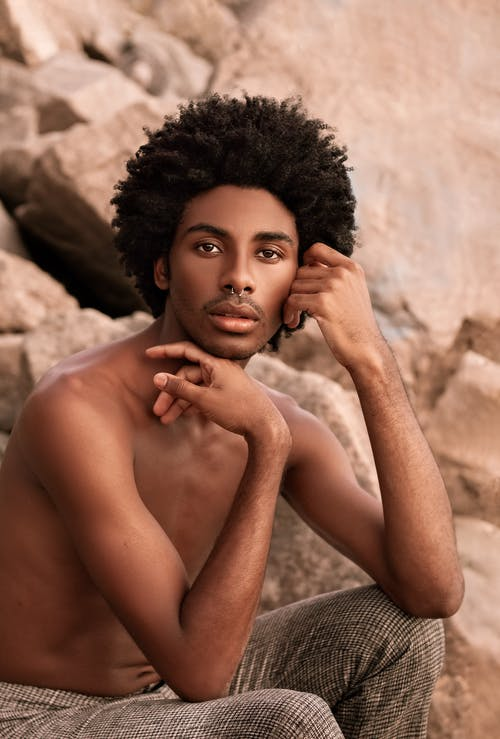 Stylish black man with Afro hairstyle on stones