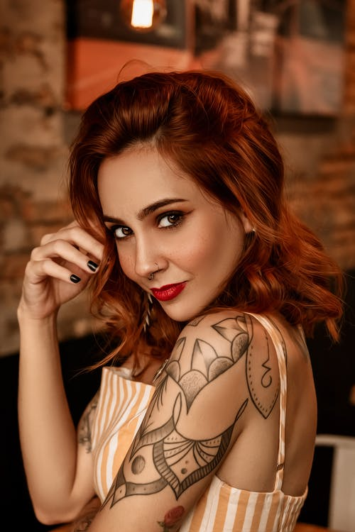 Stylish tattooed woman with red head and makeup
