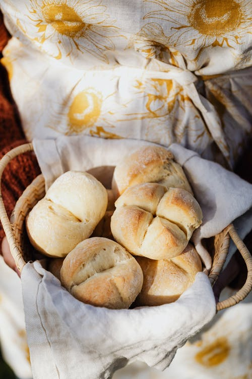 Crop female baker with fresh wheat buns on sunny day