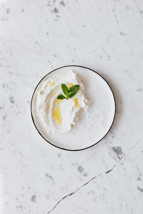Top view of composition with cottage cheese and bunch of fresh greenery in plate on white table with gray dots and crack