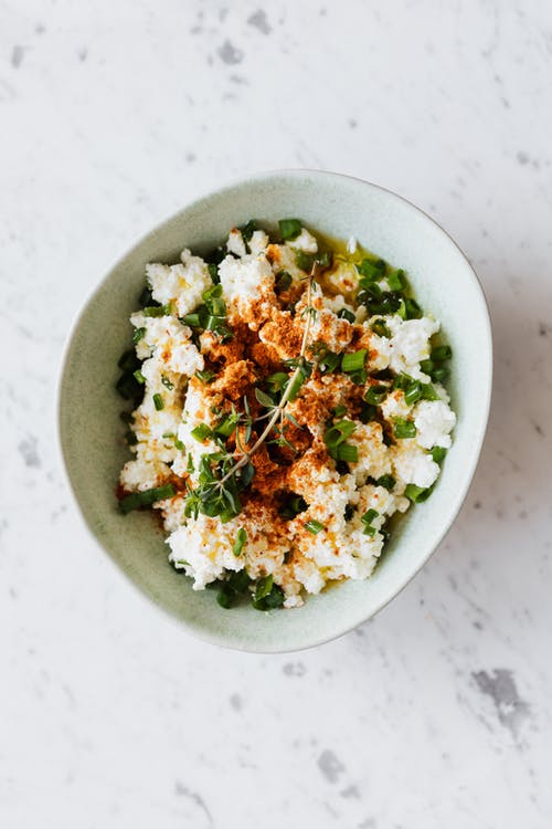 Bowl with cottage cheese and fresh herbs