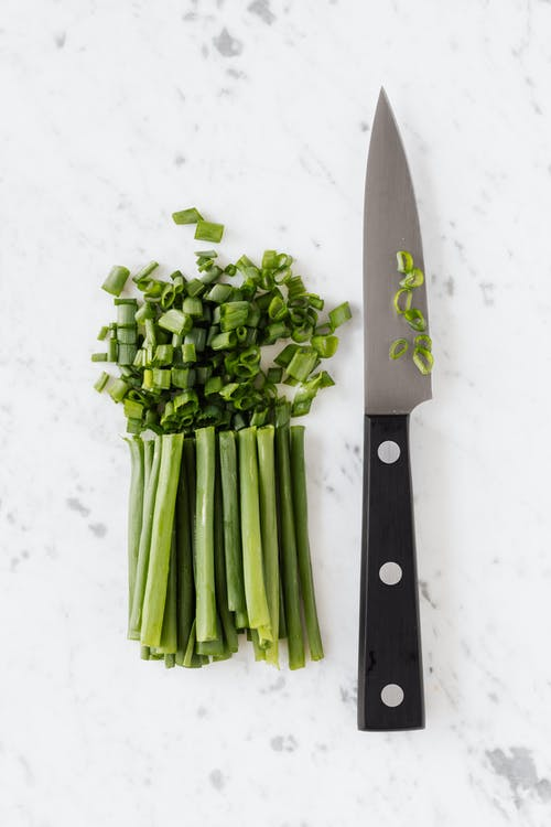 Fresh green onion and knife on white table
