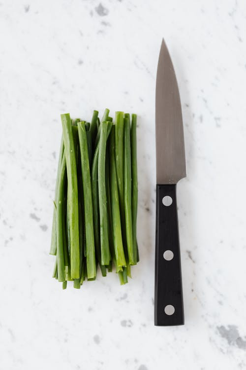 Top view of fresh spring onion and knife composed on white marble surface in kitchen